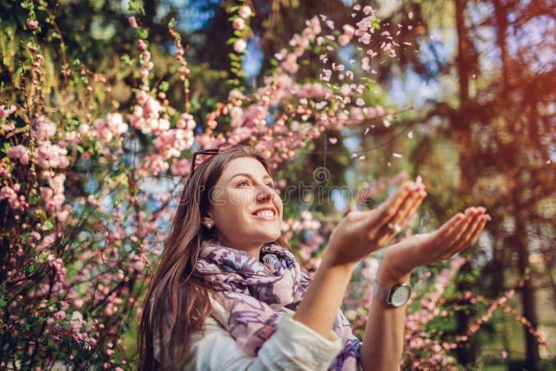 Beautiful happy woman throwing flower petals enjoying blooming spring garden. Having fun royalty free stock photography