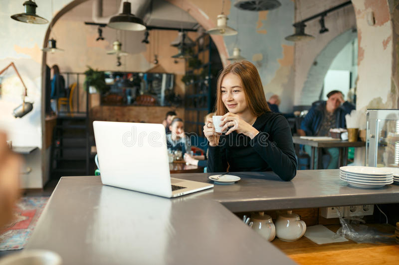 Beautiful happy woman working on laptop computer during coffee break in cafe bar stock image