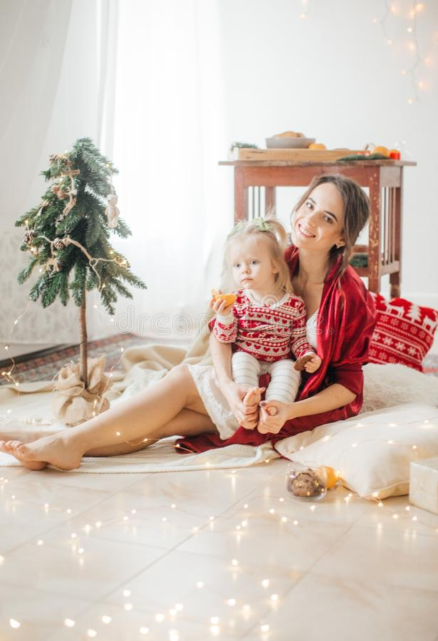 Beautiful happy woman with baby girl near a Christmas tree with gifts stock photo