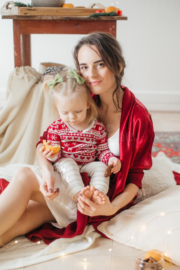 Beautiful happy woman with baby girl near a Christmas tree with gifts royalty free stock photos