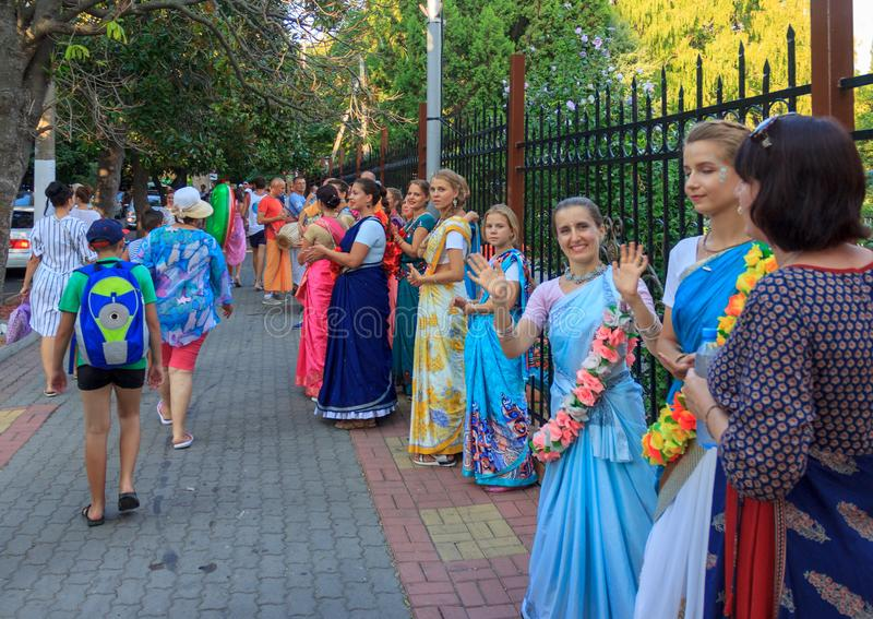 Beautiful and happy women and girls are hare Krishna in bright dresses dancing and singing on the streets of Sochi in the summer stock image