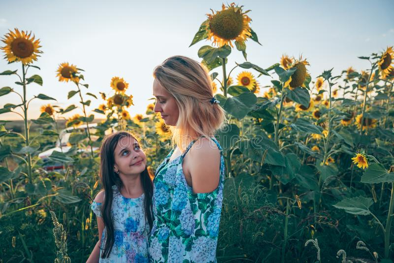 Beautiful happy young blonde mom and her brunette teen daughter smiling and looking at each other, standing among the stock images
