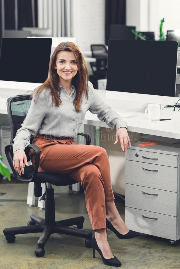 Beautiful happy young businesswoman sitting at workplace and smiling at camera royalty free stock image