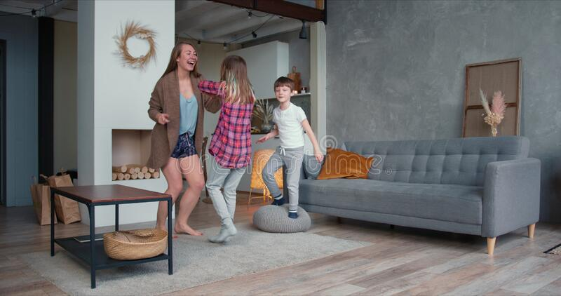 Beautiful happy young Caucasian single mom and two teen age children dancing together, have fun going crazy at home. Family love relationships on self stock images