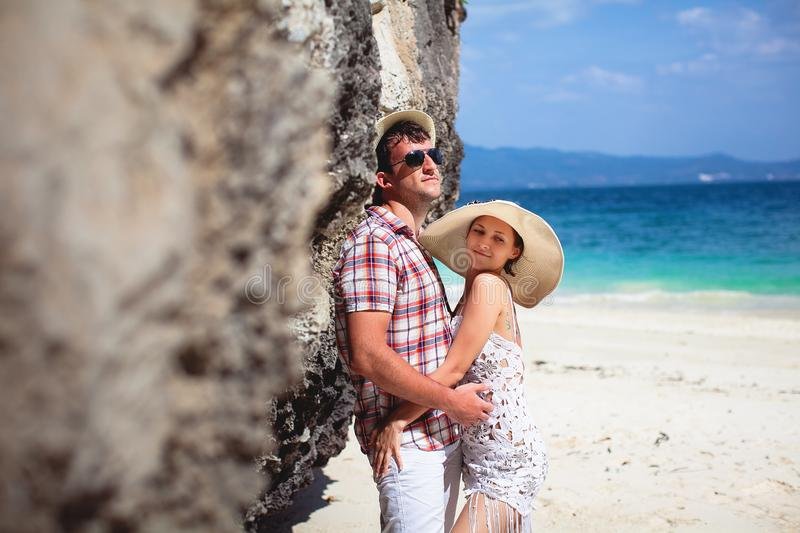 Beautiful happy young couple on the beach, against the sea and mountains on a Sunny day, outdoors. Girl and guy hugging on royalty free stock photo