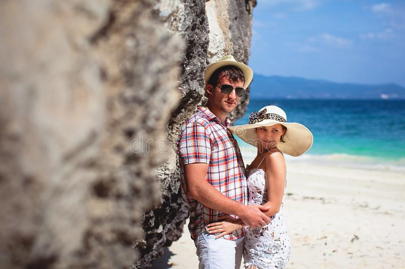 Beautiful happy young couple on the beach, against the sea and mountains on a Sunny day, outdoors. Girl and guy hugging on royalty free stock images