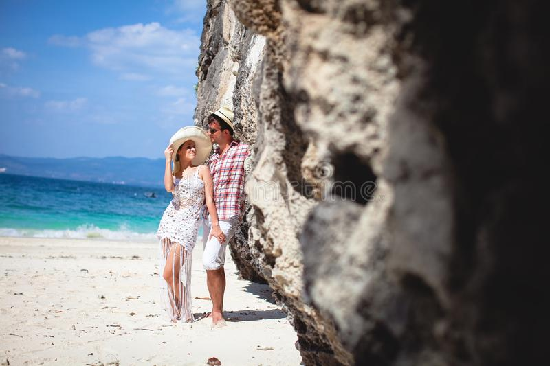 Beautiful happy young couple on the beach, against the sea and mountains on a Sunny day, outdoors. Girl and guy hugging on royalty free stock photos