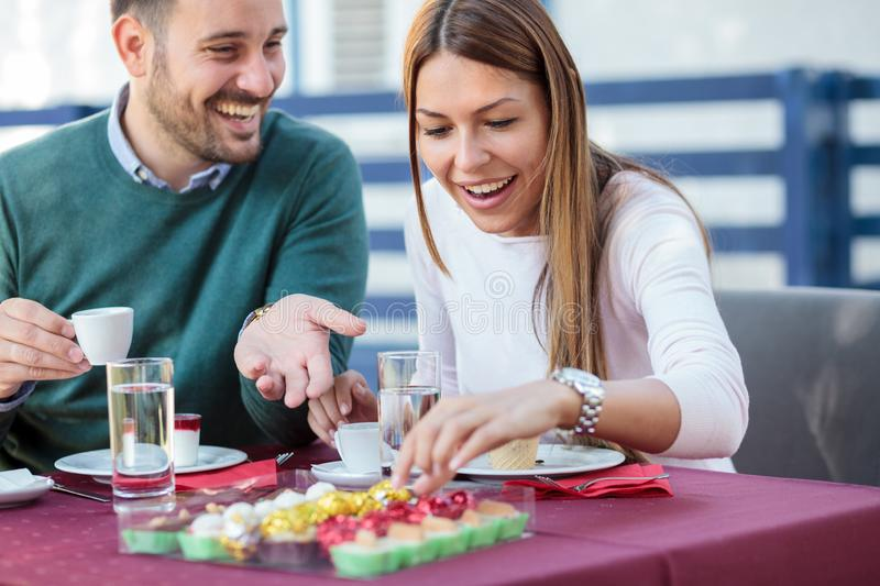 Beautiful happy young couple eating cakes and drinking coffee in a restaurant. Romantic date and anniversary celebration royalty free stock images