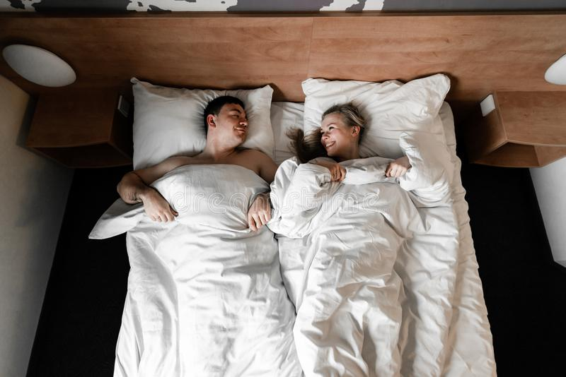 Beautiful happy young couple or family waking up together in bed royalty free stock photography