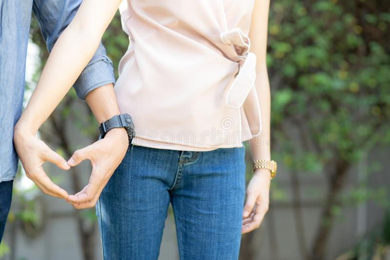 Beautiful happy young couple fun making gesture heart shape with hand outdoor together, stock image