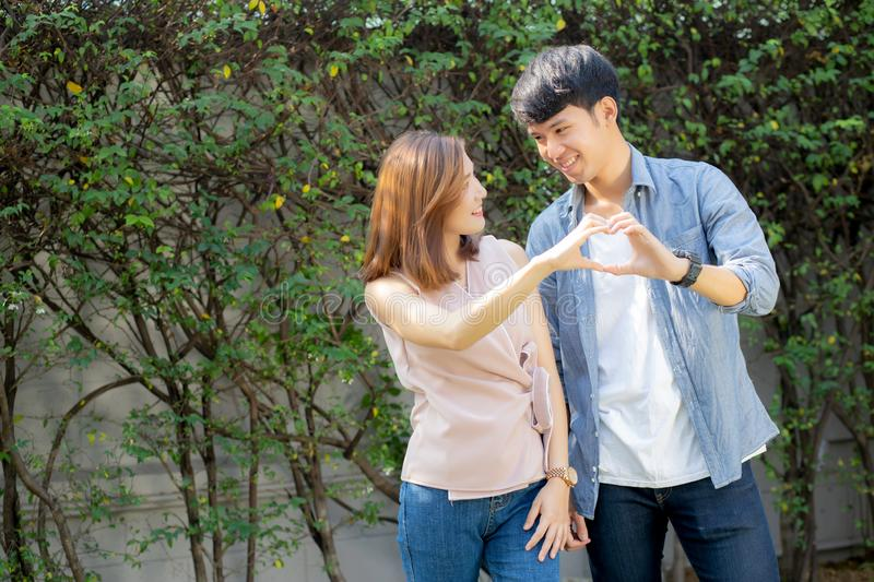 Beautiful happy young couple fun making gesture heart shape with hand outdoor together stock images