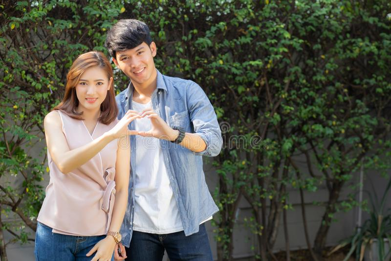Beautiful happy young couple fun making gesture heart shape with hand outdoor together stock photos