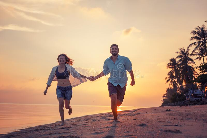 Beautiful happy young couple in love runs along the beach along the sand by the sea at sunset during a honeymoon holiday vacation royalty free stock photos