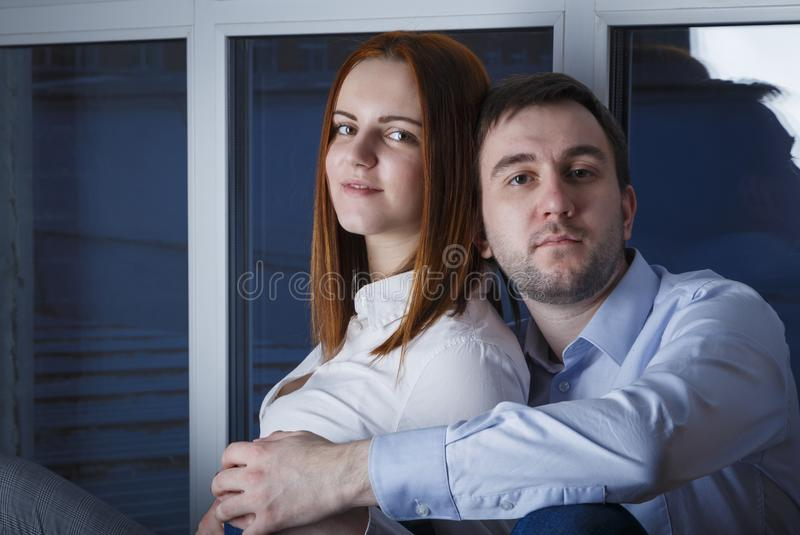 Beautiful and happy young couple man and woman sitting arm in arm on the windowsill of the home with happy faces . In the window royalty free stock images