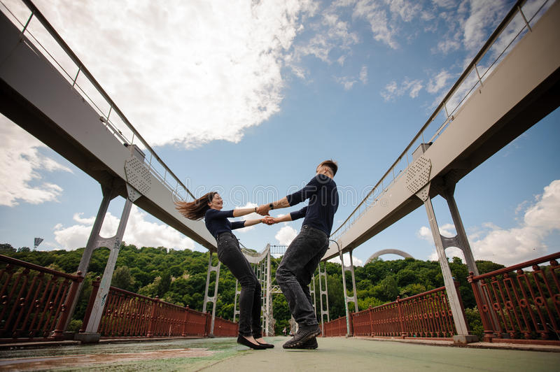 Beautiful happy young couple of man and woman spinning outdoor on bridge stock photography