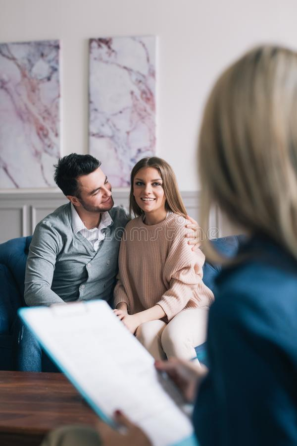 Beautiful and happy young couple visiting psychologist for relationship counselling. Psychological consultation. Beautiful and happy young couple visiting stock image