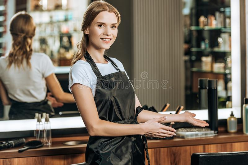Beautiful happy young female hairdresser smiling at camera royalty free stock images