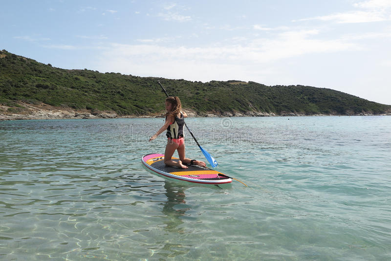 Beautiful and happy young girl learning paddle-surf royalty free stock photos