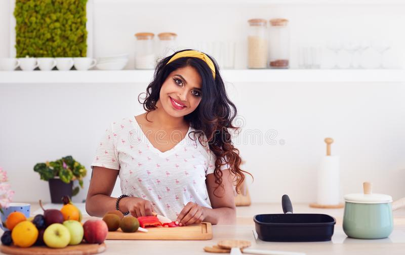 Beautiful happy young indian woman cutting vegetables on the kitchen, healthy eating royalty free stock photography