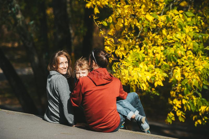 Beautiful happy young parents with little son sitting together on roadside in autumn season. Back view royalty free stock images
