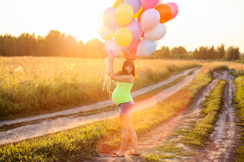 Beautiful happy young pregnant woman girl outdoors with balloons stock photo