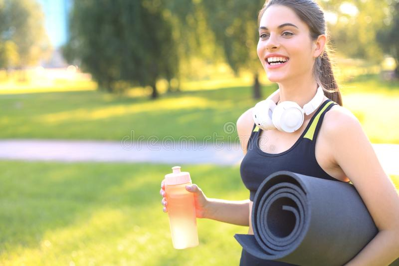 Beautiful happy young sports woman holding fitness rug in urban park stock photos