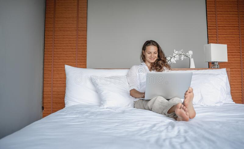 Beautiful happy young woman on bed in hotel room working on laptop, vacation business trip remote work digital nomad concept stock images
