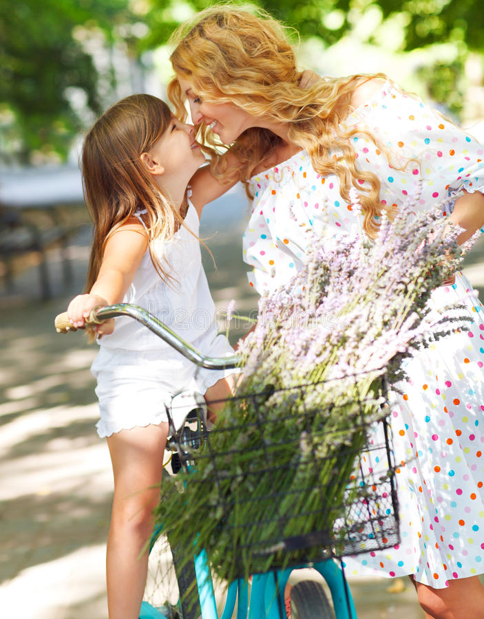 Beautiful and happy young woman on bicycle with her daughter royalty free stock image