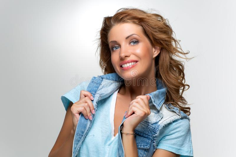 Beautiful happy girl in blue jeans jacket royalty free stock photo