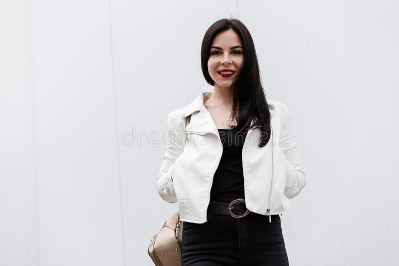 Beautiful happy young woman with a cute smile in a stylish leather jacket in a T-shirt in jeans is standing near a white building stock photo