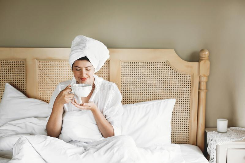 Beautiful happy young woman drinking coffee or tea in bed in hotel room or home bedroom. Stylish brunette girl in white towel royalty free stock photos