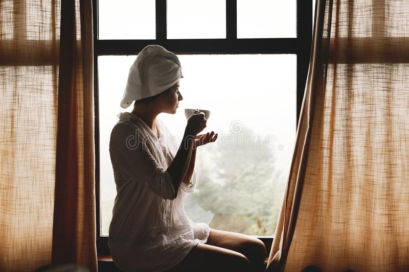 Beautiful happy young woman drinking coffee or tea, sitting at big wooden window in hotel room or home bedroom. Silhouette of girl stock photography