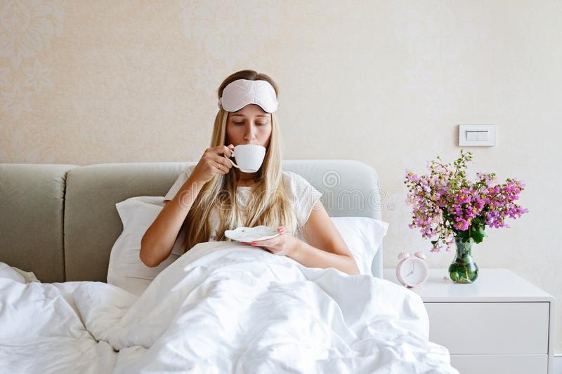 Beautiful Happy Young Woman Drinking Cup Of Coffee Or Tea While Lying In Bed After Waking Up In Morning. Portrait Of stock photography