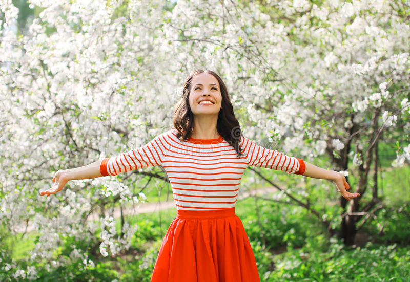 Beautiful happy young woman enjoying smell in a flowering spring royalty free stock photography