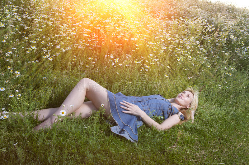The beautiful happy young woman lies in the field of camomiles stock photos