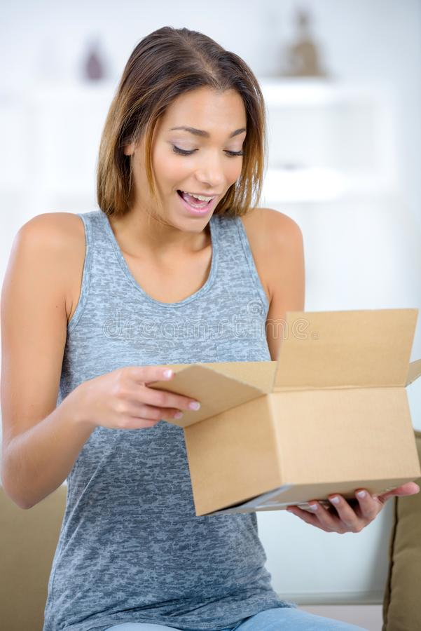 Beautiful happy young woman opening box at home royalty free stock photography