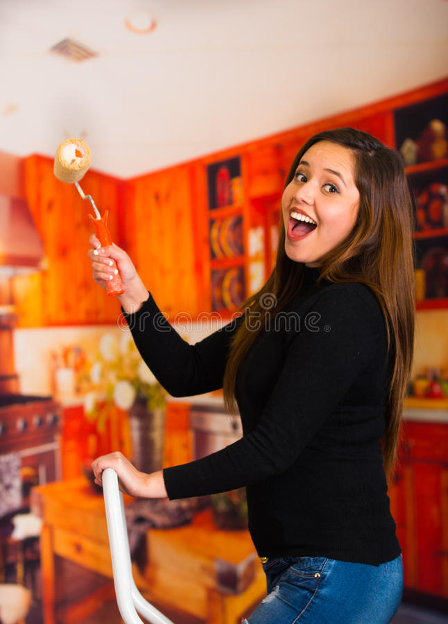 Beautiful happy young woman painting using roller stock photo