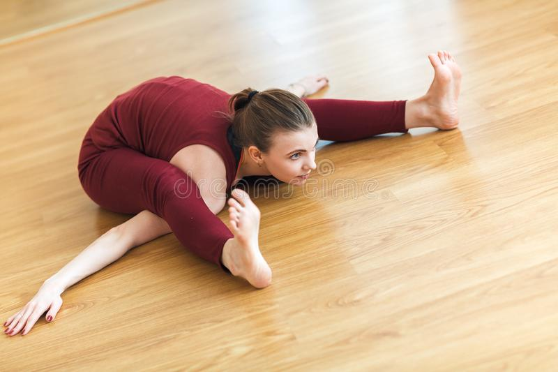 Beautiful happy young woman in red sportswear working out indoors. Girl sitting in Wide-Angle Seated Forward Bend pose, Upavishtha royalty free stock photo