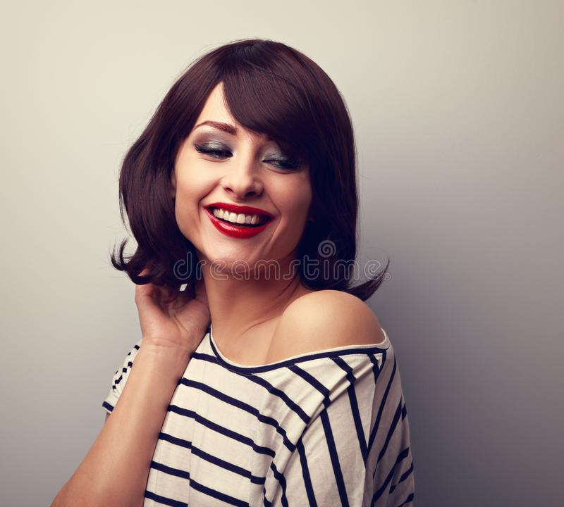 Beautiful happy young woman with short hair land red lips ooking down. Vintage toned portrait royalty free stock photography