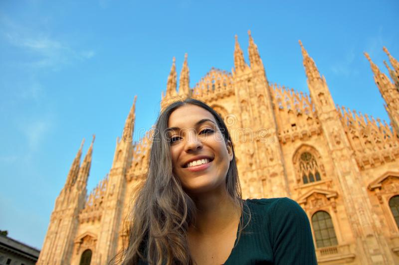 Beautiful happy young woman smiling in front of the famous Duomo Cathedral in Milan at sunset. Europe travel, Italy royalty free stock images