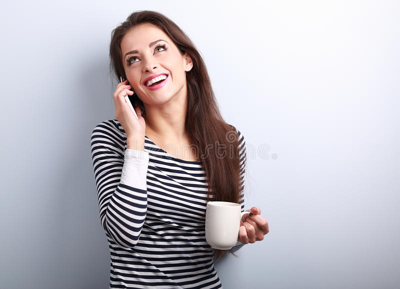 Beautiful happy young woman talking on mobile phone and drinking stock image