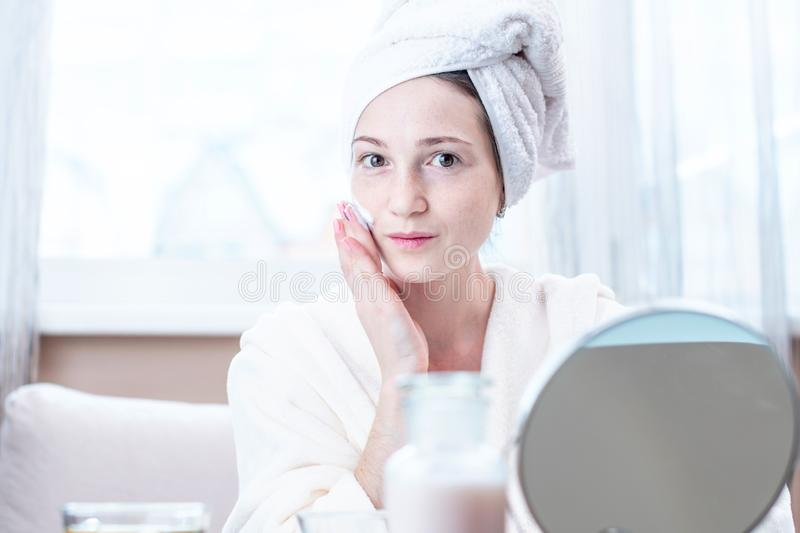 Beautiful young woman applying cream of natural cosmetics on face moisturizing the skin. Hygiene and care for the skin stock photo