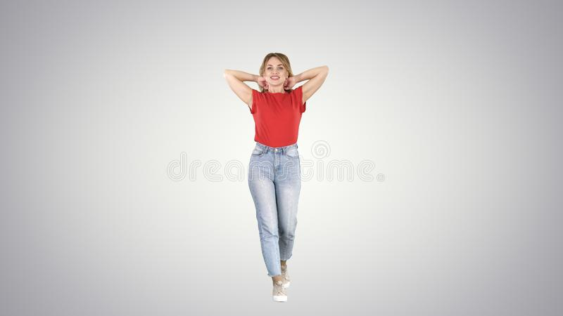 Beautiful happy young woman walking and stretching in the morning on gradient background. royalty free stock image
