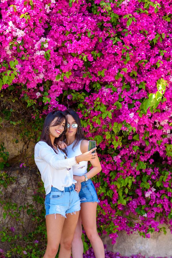 Beautiful happy young women make selfie on colorful natural background of bright pink flowers. royalty free stock photo