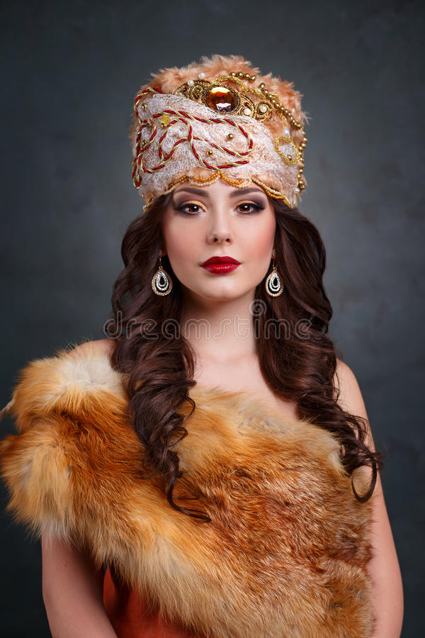 Beautiful haughty queen in royal dress. Girl in royal hat and fur coat. Luxury woman in traditional dress stock images