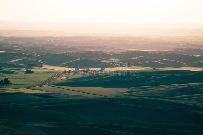 Beautiful hazy sunset from Steptoe Butte in the Palouse of Washington State, with shadows on the rolling hills of farmland.  royalty free stock photos