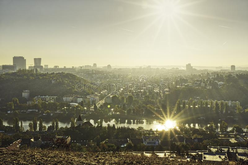 Beautiful HDR landscape panorama of Prague with sun reflected in Vltava river taken from Zvahov hill royalty free stock image