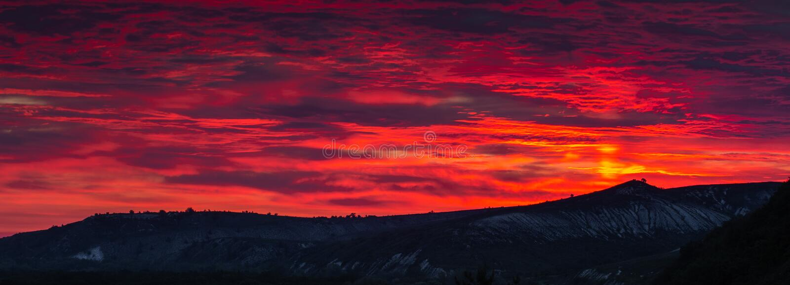 Beautiful HDR scene of late sunset with red skies over darken ground and some silhouettes of trees and hills in the far royalty free stock photography