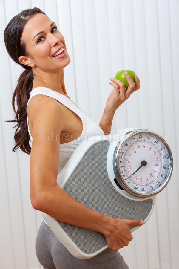 Beautiful Healthy Female Woman With Apple and Scales. Beautiful girl female young woman smiling with perfect teeth while holding apple and weighing scales royalty free stock image