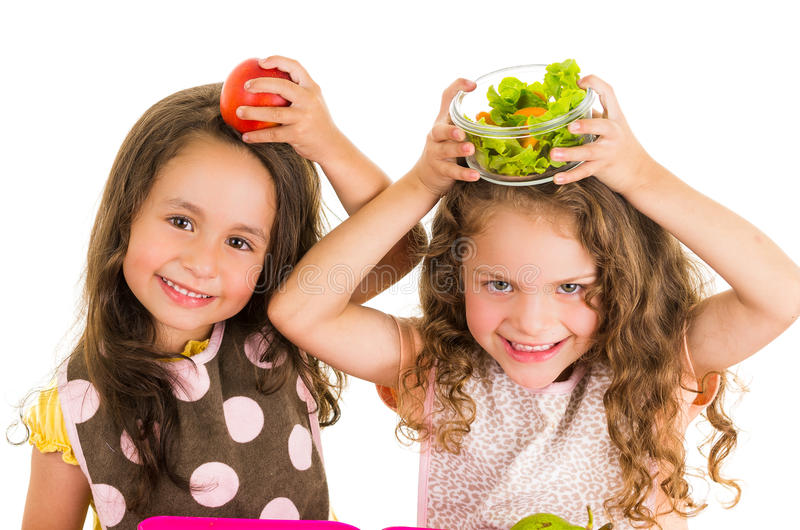 Beautiful healthy little girls holding fruits and. Vegetables on her heads isolated on white royalty free stock image